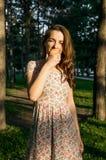 Ragazza in vestito che mangia una mela Immagine Stock Libera da Diritti
