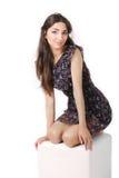 Ragazza in vestito che si siede su un cubo Fotografia Stock