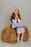 Ragazza in vestito che si siede su una balla d'annata rustica della paglia Immagini Stock