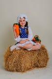 Ragazza in vestito che si siede su una balla d'annata rustica della paglia Fotografia Stock