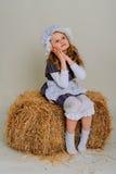 Ragazza in vestito che si siede su una balla d'annata rustica della paglia Fotografia Stock Libera da Diritti