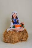Ragazza in vestito che si siede su una balla d'annata rustica della paglia Immagine Stock