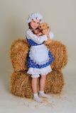 Ragazza in vestito che sta vicino ad un fieno d'annata rustico con un giocattolo Fotografia Stock Libera da Diritti