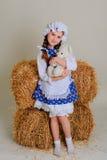 Ragazza in vestito che sta vicino ad un fieno d'annata rustico con un giocattolo Fotografie Stock