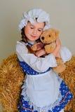 Ragazza in vestito che sta vicino ad un fieno d'annata rustico con un giocattolo Fotografie Stock Libere da Diritti