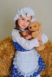 Ragazza in vestito che sta vicino ad un fieno d'annata rustico con un giocattolo Fotografia Stock