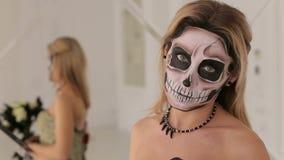 Ragazza in vestito con un mazzo dei fiori neri e del trucco sotto forma di scheletro archivi video