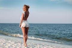 Ragazza in vestito da estate che sta su una spiaggia e che guarda al mare fotografia stock libera da diritti