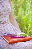 Ragazza in vestito da estate che tiene un libro Fotografie Stock Libere da Diritti