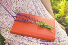 Ragazza in vestito da estate che tiene un libro Fotografie Stock
