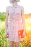 Ragazza in vestito da estate che tiene un libro Immagine Stock Libera da Diritti