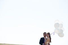 Ragazza in vestito da sposa e husbad con gli impulsi in mani Immagine Stock