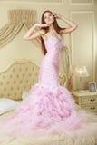 Ragazza in vestito da sposa rosa che resta sul letto Fotografia Stock