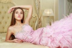 Ragazza in vestito da sposa rosa sul letto Fotografia Stock