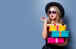Ragazza in vestito e cappello neri con i contenitori di regalo immagini stock