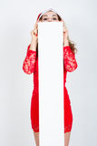 Ragazza in vestito e cappello rossi di Santa con le insegne bianche in bianco Immagini Stock Libere da Diritti