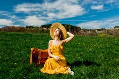 Ragazza in vestito giallo e valigia che si siedono sul prato della montagna con i denti di leone fotografia stock