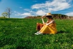Ragazza in vestito giallo e valigia che si siedono sul prato della montagna con i denti di leone immagini stock libere da diritti