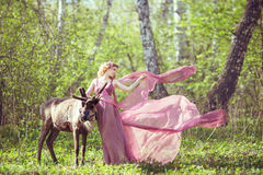 Ragazza in vestito leggiadramente con un treno scorrente sul vestito e sulla renna Immagine Stock