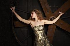 Ragazza in vestito lucido dal broccato contro sopra una parte posteriore di oscurità Fotografie Stock