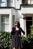 Ragazza in vestito nero con i pois e gli occhiali da sole Fotografia Stock
