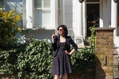 Ragazza in vestito nero con i pois e gli occhiali da sole Fotografie Stock Libere da Diritti
