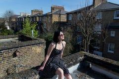 Ragazza in vestito nero dal pois che si siede sul roo Fotografie Stock