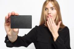 Ragazza in vestito nero e con le labbra rosse, con la carta di credito a disposizione, fotografie stock