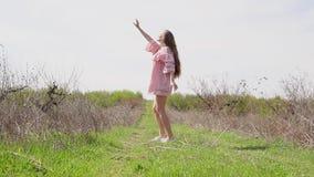 Ragazza in vestito rosa che posa nel giardino video d archivio