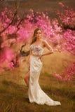 Ragazza in vestito rosa in giardini di fioritura fotografia stock