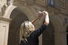 Ragazza in vestito rosso che prende immagine a Montserrat, Santa Maria de Montserrat, vicino a Barcellona, la Spagna immagine stock