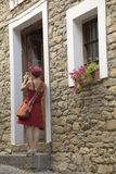 Ragazza in vestito rosso che prende immagine in villaggio di Ainsa, Spagna Fotografia Stock