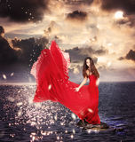 Ragazza in vestito rosso che si leva in piedi sulle rocce dell'oceano Fotografia Stock Libera da Diritti