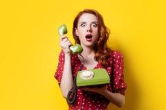 Ragazza in vestito rosso con il telefono di quadrante verde immagine stock