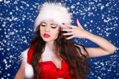 Ragazza in vestito rosso dal Babbo Natale che propone sulla neve Immagini Stock