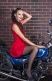 Ragazza in vestito rosso su un motociclo Fotografie Stock Libere da Diritti