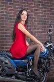 Ragazza in vestito rosso su un motociclo Immagini Stock