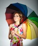 Ragazza in vestito variopinto che si leva in piedi sotto l'ombrello Fotografia Stock