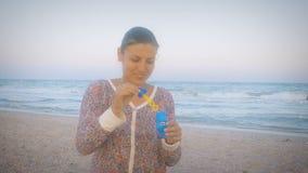 Ragazza in vestito variopinto che soffia le bolle di sapone sulla spiaggia contro il contesto del mare un giorno ventoso stock footage