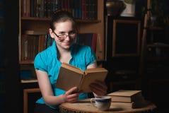 Ragazza in vetri che legge un libro Immagine Stock Libera da Diritti