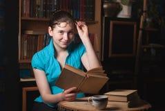 Ragazza in vetri che legge un libro Immagine Stock