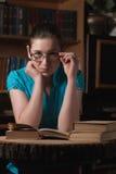 Ragazza in vetri che legge un libro Immagini Stock