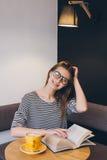 Ragazza in vetri che legge un libro in una caffetteria Immagini Stock Libere da Diritti