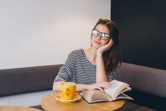 Ragazza in vetri che legge un libro in una caffetteria Immagine Stock Libera da Diritti
