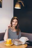 Ragazza in vetri che legge un libro in una caffetteria Fotografia Stock Libera da Diritti
