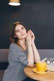 Ragazza in vetri che legge un libro in una caffetteria Fotografie Stock Libere da Diritti
