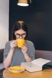 Ragazza in vetri che legge un libro in una caffetteria Fotografia Stock