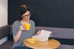 Ragazza in vetri che legge un libro in una caffetteria Fotografie Stock
