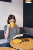Ragazza in vetri che legge un libro in una caffetteria Immagini Stock