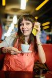 Ragazza in vetri con un telefono in un caffè Fotografia Stock Libera da Diritti